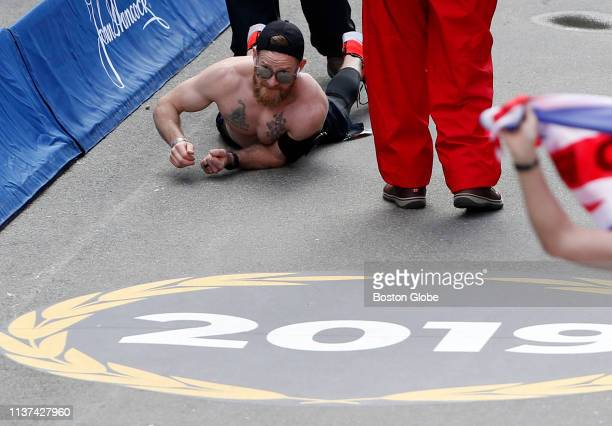 A runner crawls down Boylston Street towards the finish line of the 123rd Boston Marathon in Boston on April 15 2019