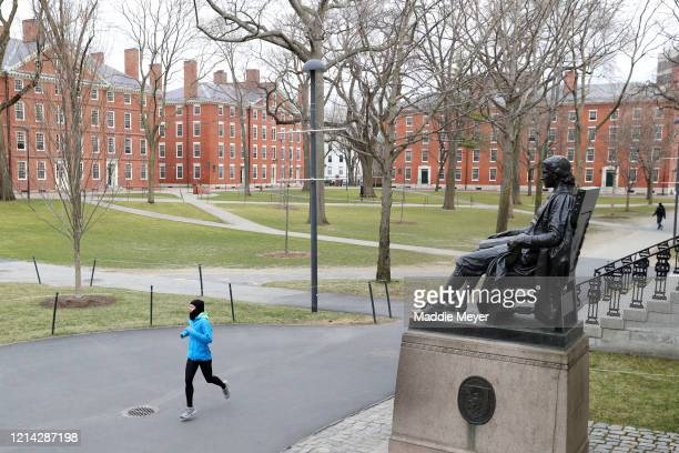 Runner crosses Harvard Yard on March 23, 2020 in Cambridge, Massachusetts. Students were required to be out of their dorms no later than March 15 and...