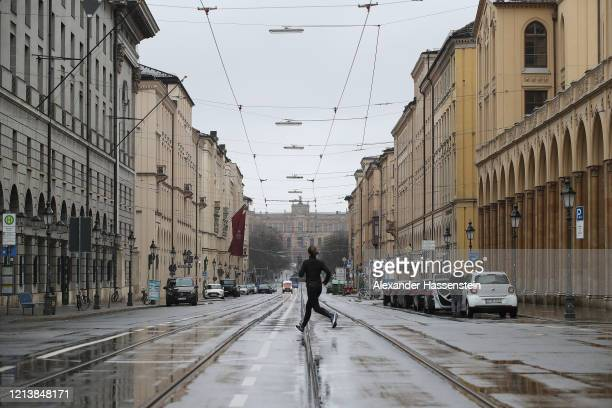 A runner crosses the Maximilianstrasse with the Maximilianeum a palatial building in Munich in the background normally a magnet for tourists as they...