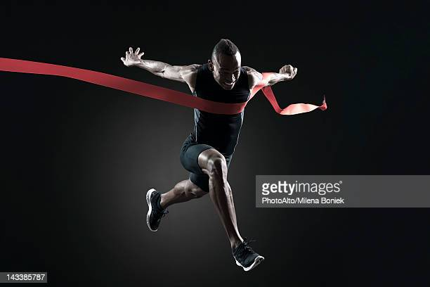 runner crossing finish line - finish line stock pictures, royalty-free photos & images