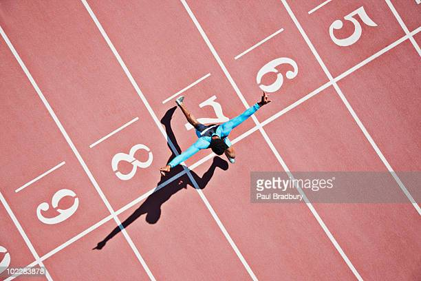runner crossing finishing line on track - rennen stockfoto's en -beelden