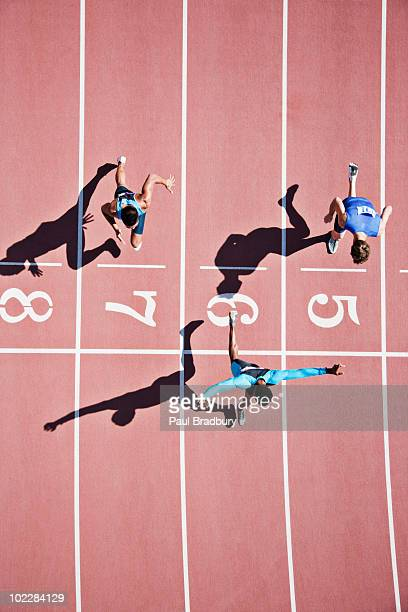 runner crossing finishing line on track - rivaliteit stockfoto's en -beelden