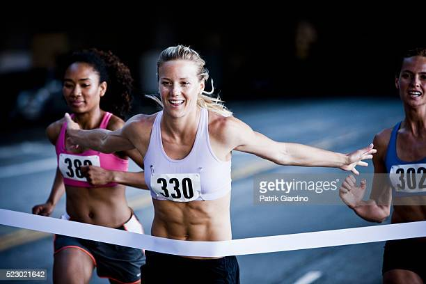 runner crossing the finish line - finishing line stock pictures, royalty-free photos & images