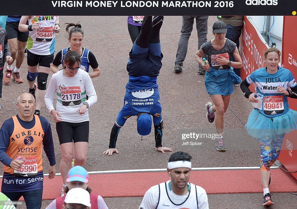 A runner does a hand stand as they cross the finish line on The Mall during the Virgin Money London Marathon on April 24, 2016 in London, England.