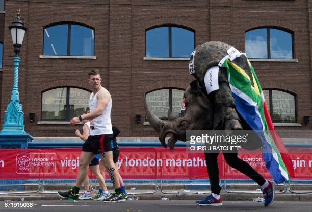 A runner dressed as a rhino crosses the half way point and past a sign in a window reading '13 miles to prosecco' on Tower Bridge during the London...
