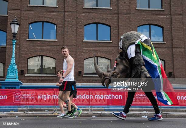 TOPSHOT A runner dressed as a rhino crosses the half way point past a sign in a window reading '13 miles to prosecco' on Tower Bridge during the...