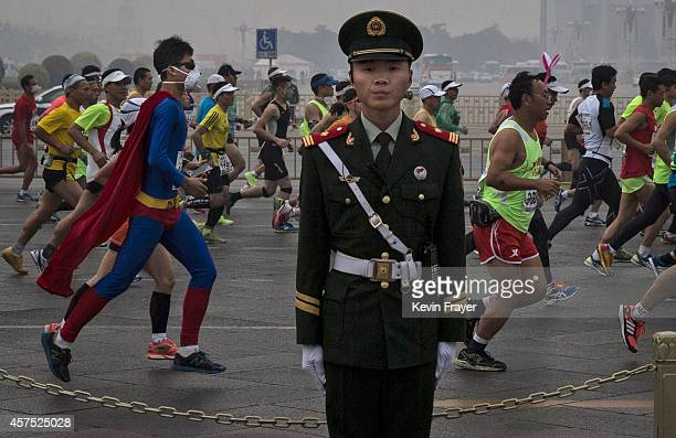 A runner dressed as 'Superman' wears a mask as he and others run past a Chinese soldier during the Beijing Marathon near Tiananmen Square October 19...