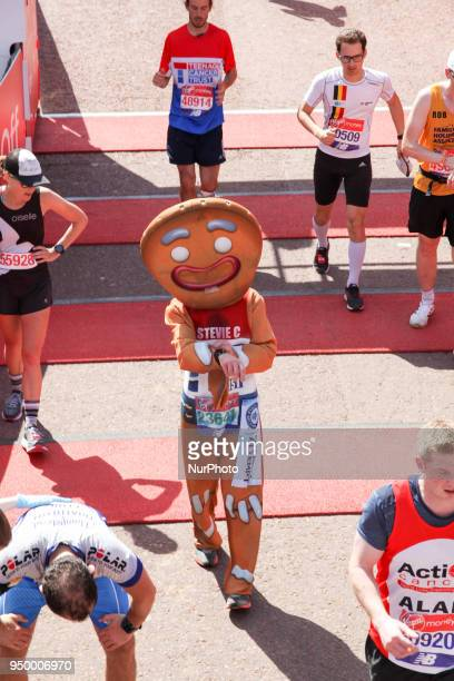 Runner dressed as the Gingerbread Man crosses the finish line during the 2018 London Marathon in central London on April 22, 2018.