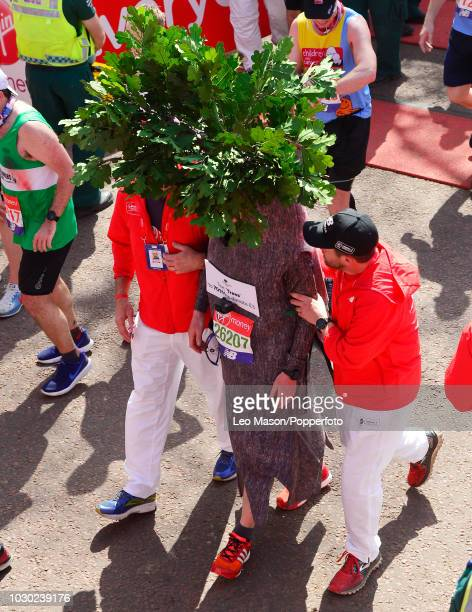 A runner dressed in fancy dress costume is assisted at the finish on The Mall during The Virgin London Marathon on April 22 2018 in London England