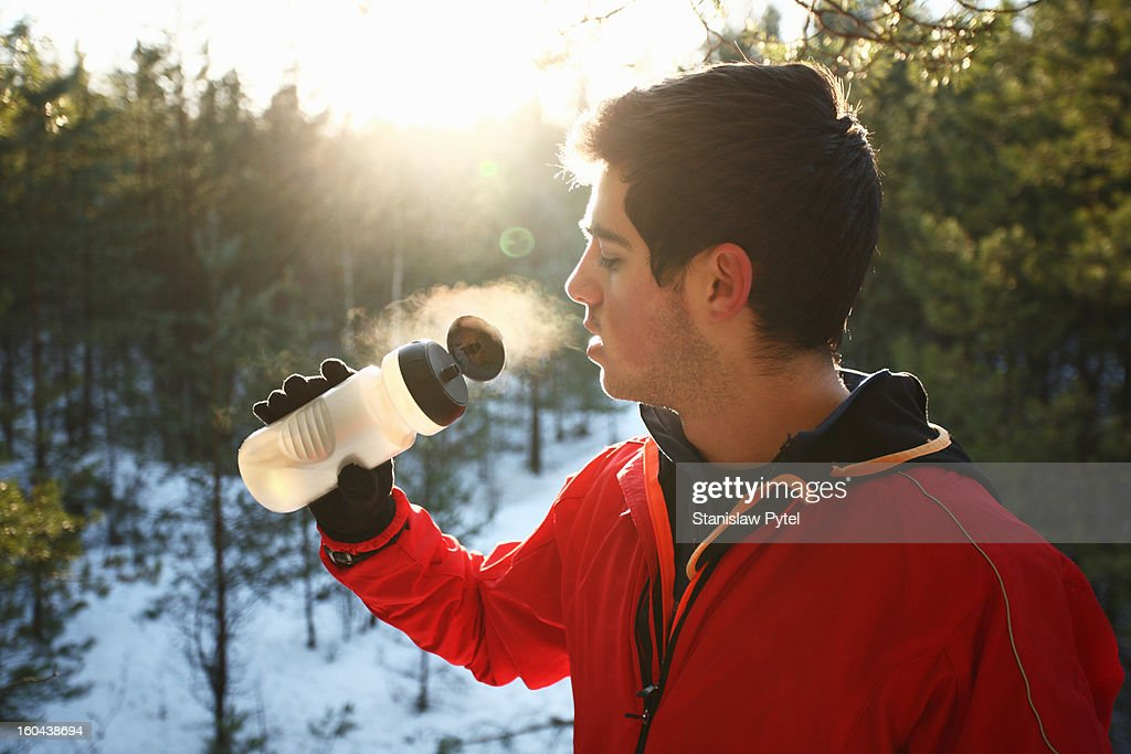 Runner drinking water in forest : Stock Photo