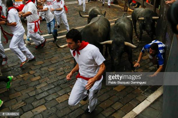 A runner falls as revellers run with Jose Escolar Gil's fighting bulls at Curva Estafeta during the third day of the San Fermin Running of the Bulls...