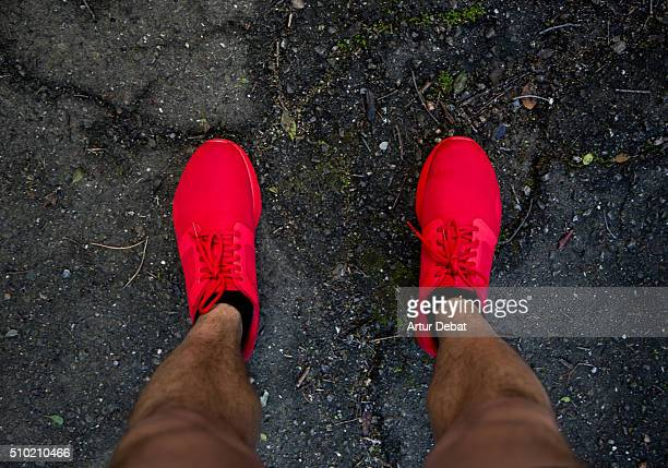 Runner from personal point of view with his red trainers with black asphalt.