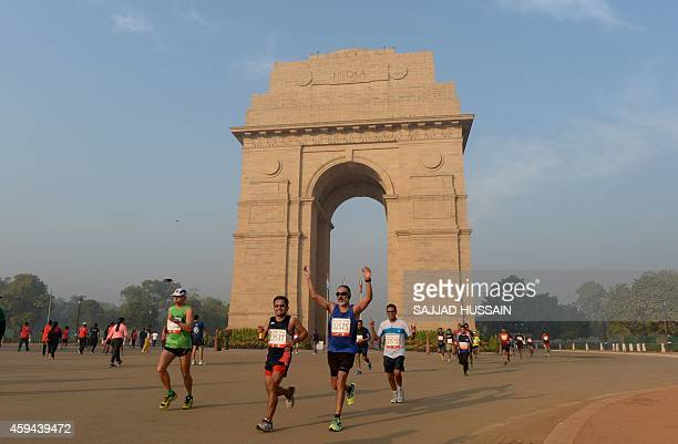 A runner gestures as he and others pass by the India Gate monument during the Delhi half marathon in New Delhi on November 23 2014 Ethiopian runner...