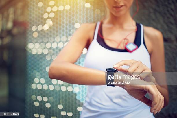 runner girl is checking her smart watch - smart watch stock pictures, royalty-free photos & images