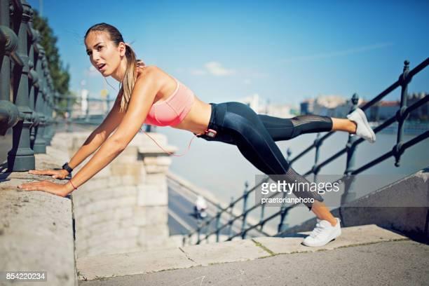 Runner girl is doing push ups along the river