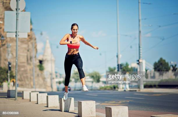 runner girl is jumping on the blocks and keeping balance - hot body girls stock photos and pictures