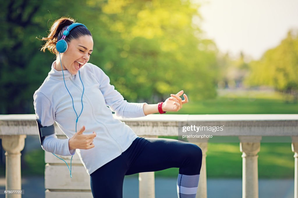 Runner girl is pretend playing guitar at her favorite song : Stock Photo