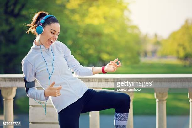 runner girl is pretend playing guitar at her favorite song - musical stock pictures, royalty-free photos & images