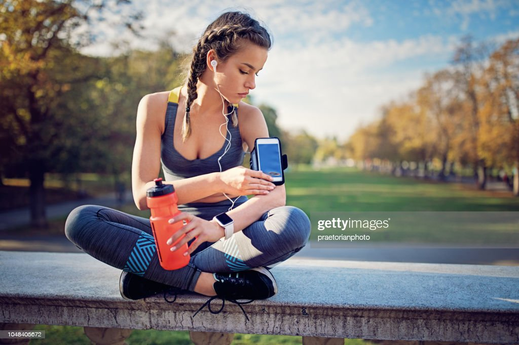Runner girl is resting and checking her arm band in the park : Stock Photo