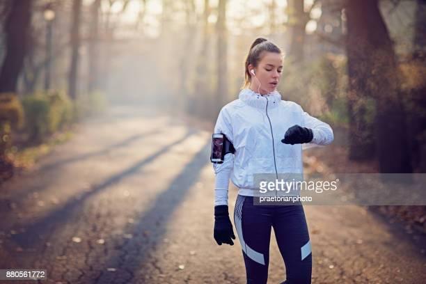 Läufer-Mädchen ist ruhen und nebligen Morgen ihr smart Uhr einchecken