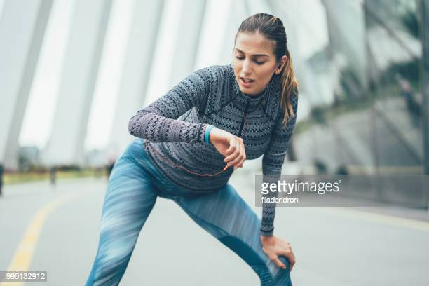 läufer-mädchen ist ausruhen und überprüfung ihrer smartwatch - sportlerin stock-fotos und bilder