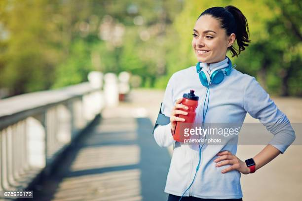Runner girl is resting and drinking water