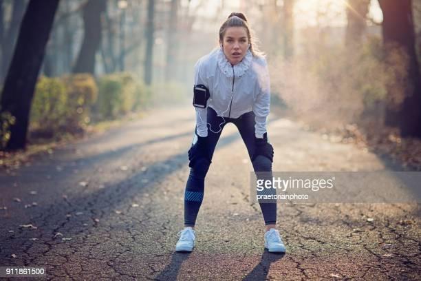 runner meisje is uitgeput in de mistige ochtend rusten - atlete stockfoto's en -beelden