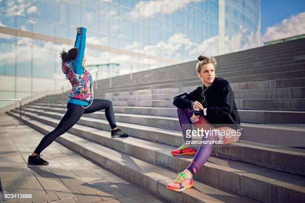 Runner girl is resting on the city stairs and checking her smart watch