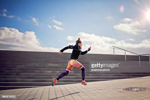 runner girl is sprinting - corredor caraterística de construção imagens e fotografias de stock