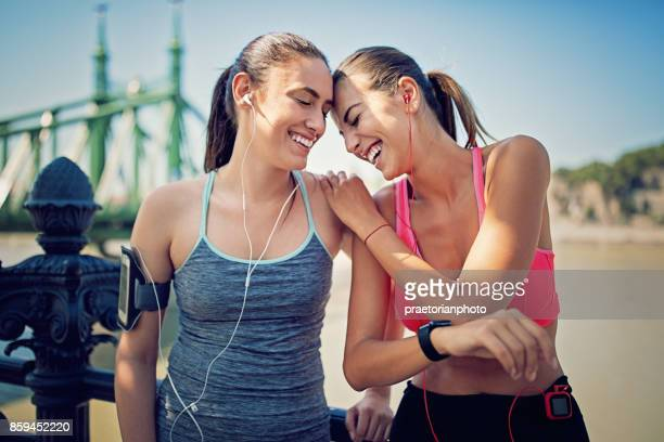 Runner girls are resting along the river and making fun together