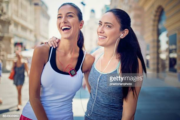runner girls are resting on the pedestrian street in the city center - center athlete stock photos and pictures