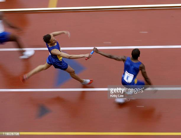 A runner hands off baton in the boys high school 1600meter heats in the111th Penn Relays at the University of Pennsylvania's Franklin Field in...