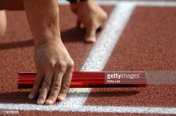 A runner holds a baton in the starting blocks in the 1600meter relay at the Trojan Relays at Cromwell Field in Los Angeles Calif on Saturday March 3...
