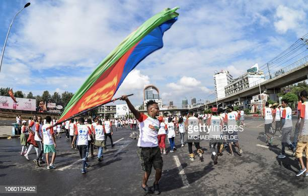 A runner holds Eritrea's national flag during the first EthiopiaEritrea Peace and reconciliation Run in Addis Ababa on November 11 2018 Thousands of...