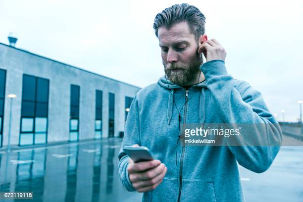 Läufer hält Smartphone und setzt Kopfhörer im Ohr
