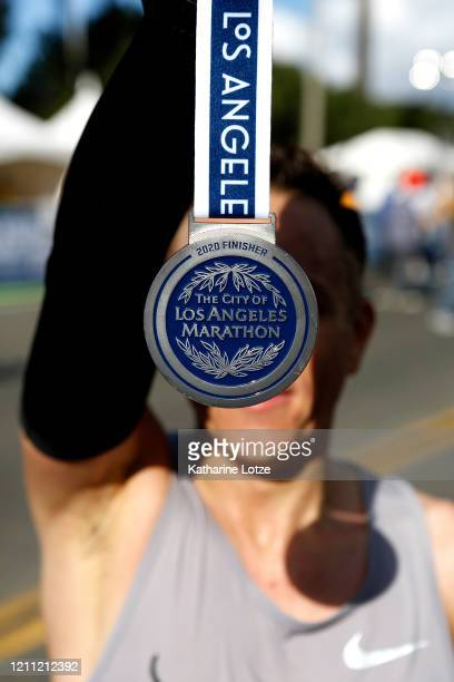 A runner holds up a finisher's medal following the 2020 Los Angeles Marathon on March 08 2020 in Los Angeles California