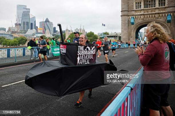 Runner in a submarine costume crosses Tower Bridge during the 2021 Big Half Marathon in central London on August 22, 2021. - The Vitality Big Half...
