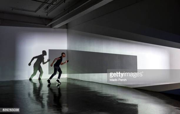 Runner in an abstract space with graphic shape projected on to him