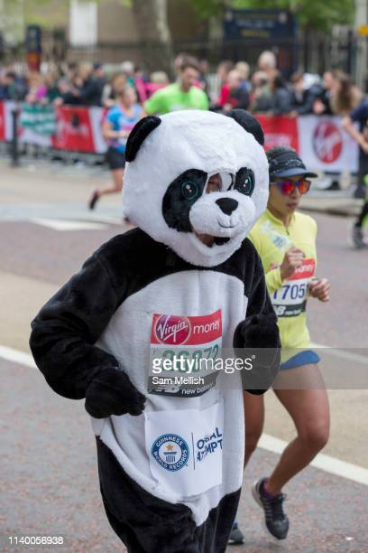 A runner in dressed as a panda bear on Birdcage Walk during The Virgin London Marathon on 28th April 2019 in London in the United Kingdom Now in its...