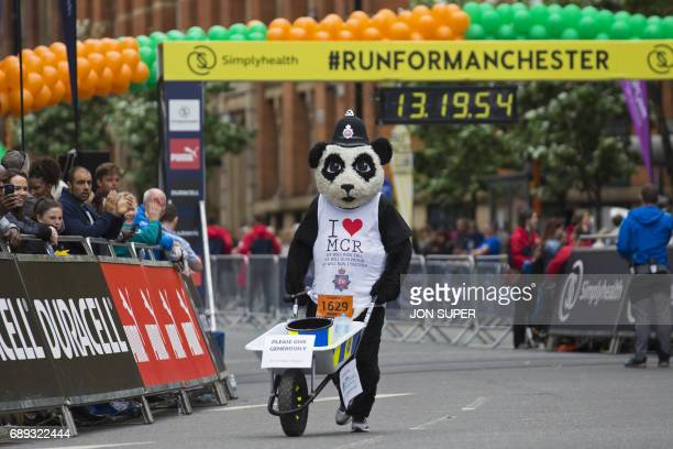 A runner in fancy dress collects money for the victims of the Manchester Arena bombing at the start of the Great Manchester Run in Manchester north...