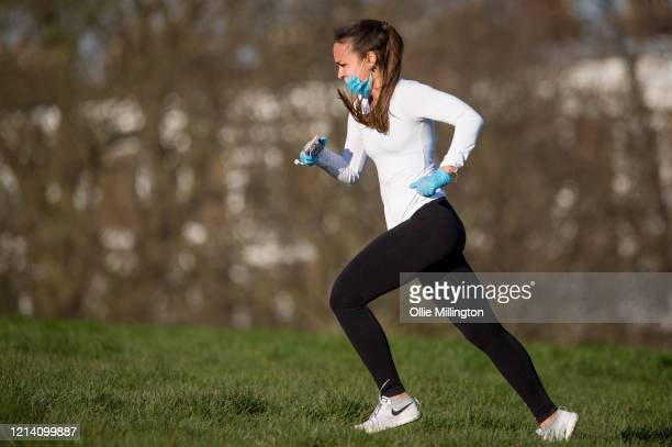 A runner in gloves and a mask as members of the public seen congregating with friends on Primrose Hill not observing public distancing emergency...