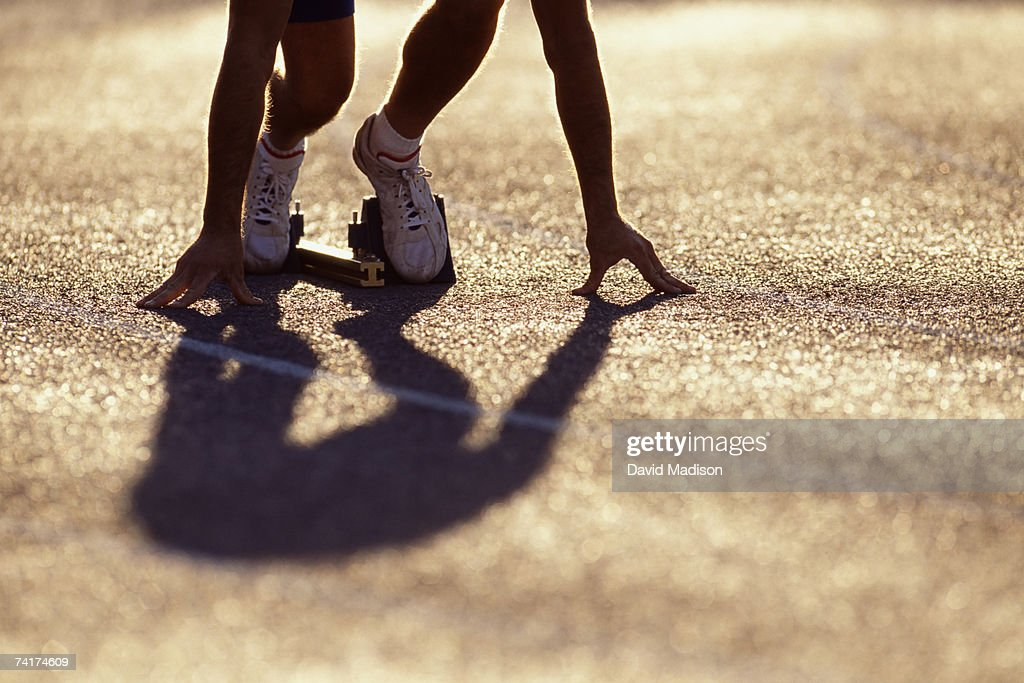'Runner in position at starting block, low section' : Stock Photo