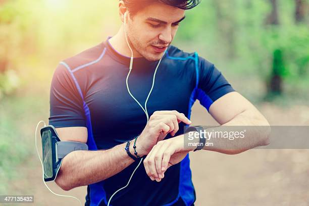 runner in the park using smart watch - checking sports stock pictures, royalty-free photos & images