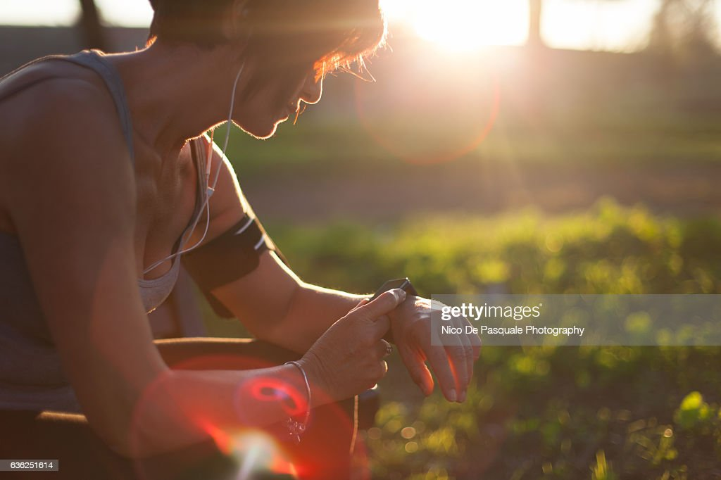 Runner in the park using smart watch : Stock Photo
