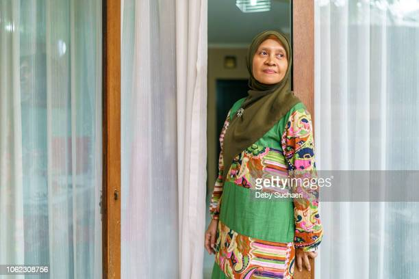 possitive and confident muslim woman wearing colorful cloths standing by the door at home