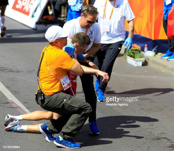 A runner is carried after collapsing at the finish line of the Men's Marathon final race during the 2018 European Athletics Championships at...