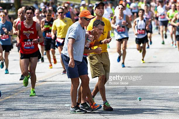 A runner is helped off the course after falling along Commonwealth Avenue near 'Heartbreak Hill' in Newton Mass during the 120th Boston Marathon on...