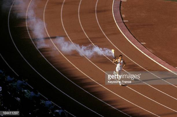 A runner is holding the Olympic Flame during the Olympic Games opening ceremony in Tokyo