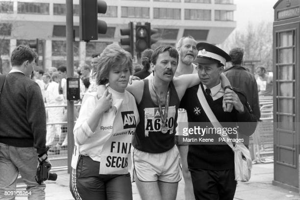 A runner is lead away from the finish by another runner and a St John's ambulanceman after finishing the Marathon