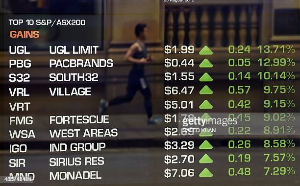 A runner is reflected in a window as data on an electronic share board is seen at the Australian Stock Exchange in Sydney on August 25 2015...